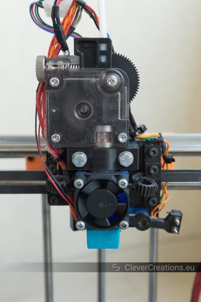 Close-up of an extruder carriage in a 3D printer with an E3D Titan geared extruder and a servo Z-probe.