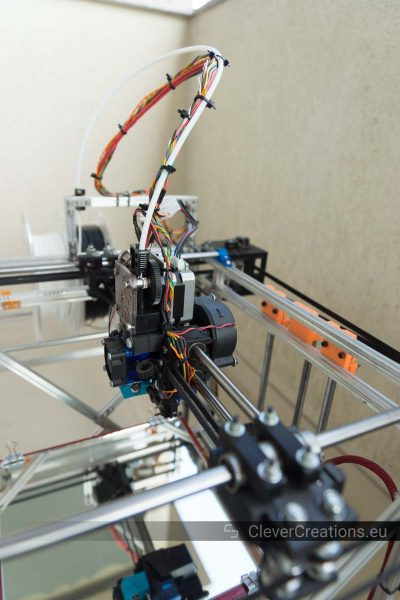 An extruder carriage in a coreXY printer with a PTFE tube and wires extending from it.