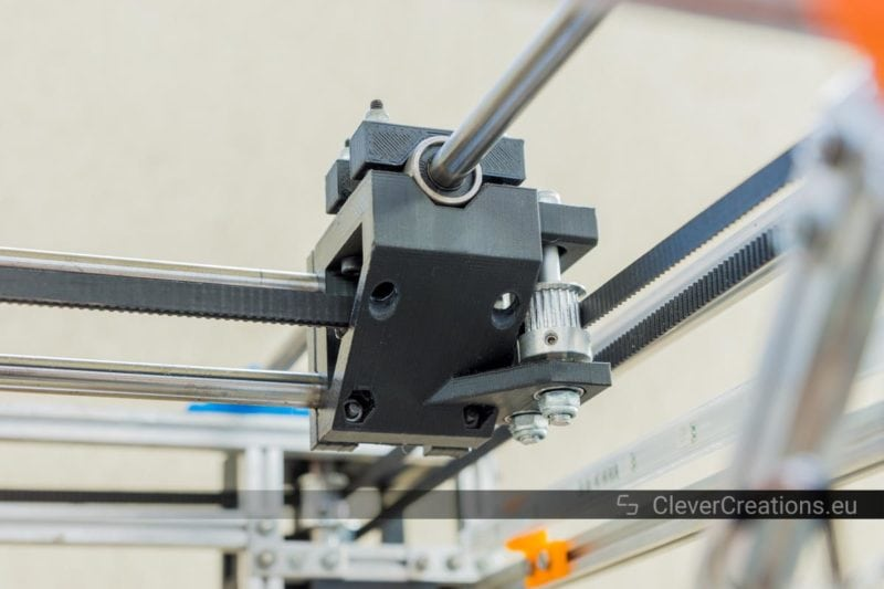A 3D printed Y carriage in a coreXY 3D printer with pulleys and linear rods attached to it, timing belts are routed through the Y carriage.