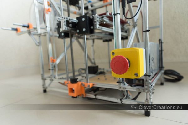 A custom 3D printer built from Makerbeams with in focus a red with yellow emergency button.