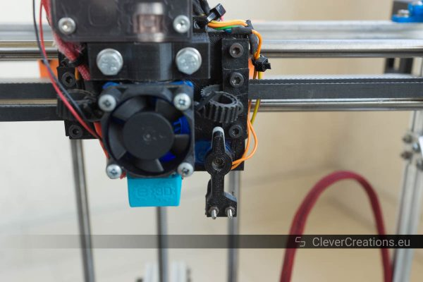 Close-up of an extended servo arm with a Z-probe on an extruder carriage, inside of a 3D printer.