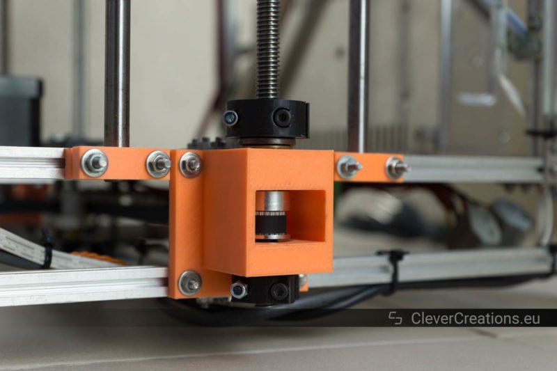 Close-up of a 3D printed Z-stage bearing holder in a 3D printer, containing a GT2 pulley, a thrust bearing, clamps and threaded rod.