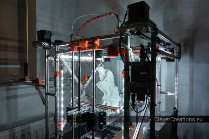 A DIY coreXY 3D printer with LED strips lighting up a completed 3D print.