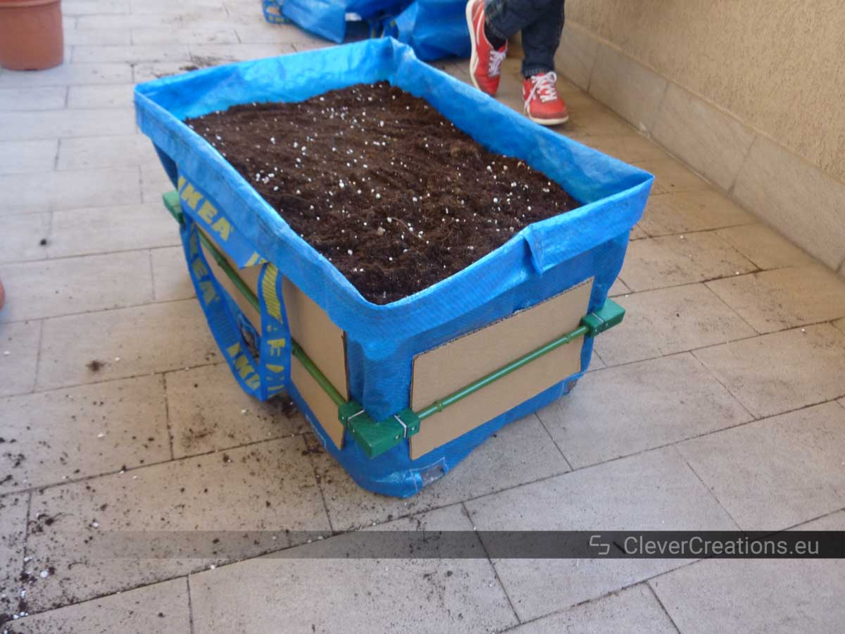A DIY IKEA FRAKTA grow bag filled with potting soil.