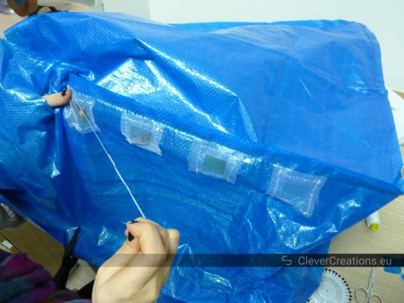 A a pair of hands using a sewing needle to sew a square piece of window mesh to an IKEA bag.
