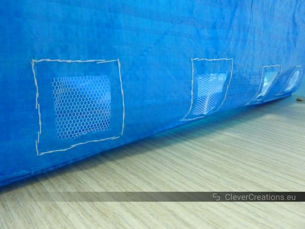 The outside of an IKEA FRAKTA bag with four drainage holes that are covered by window mesh.