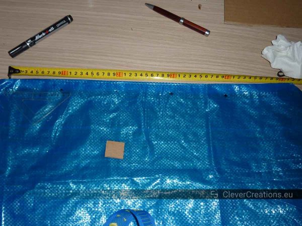 An IKEA FRAKTA bag with dotted markings, next to it an extended measuring tape and some pens.
