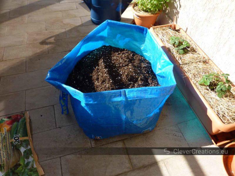 A DIY IKEA FRAKTA DIY grow bag filled with potting soil next to several other plants on a tiled floor.