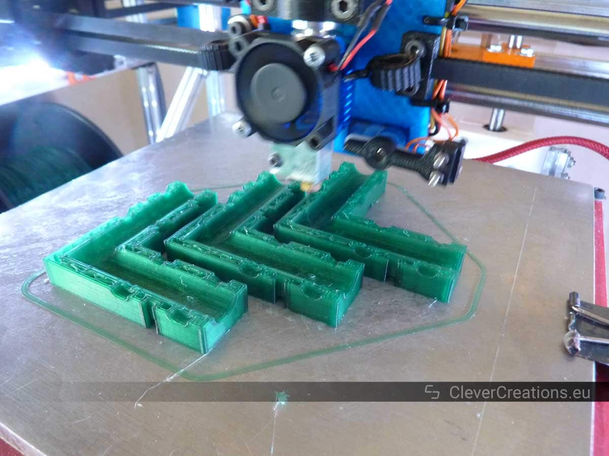 A 3D printer printing three green corner components for a frame.
