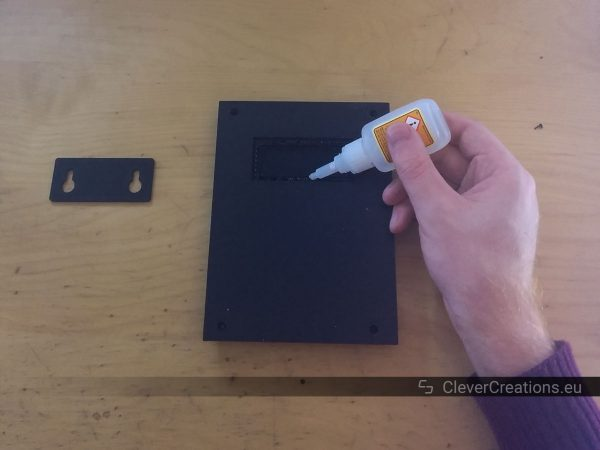 A hand holding a bottle of super glue over a black 3D printed part on a desk.
