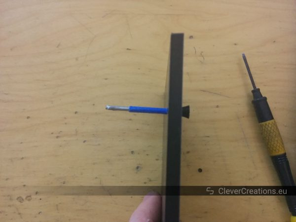 Side view of a nail sticking out of a black 3D printed part, with a piece of blue tape wrapped around the nail.