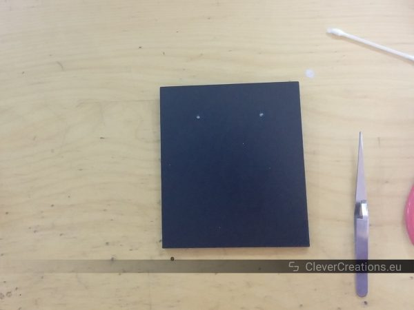 A black 3D printed part with two pieces of nail glued into place on a desk, with next to it a pair of tweezers.