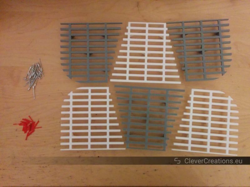Top view of six grey and white 3D printed grid pieces, a handful of steel rivets and a handful of thin red bars on a wooden surface.