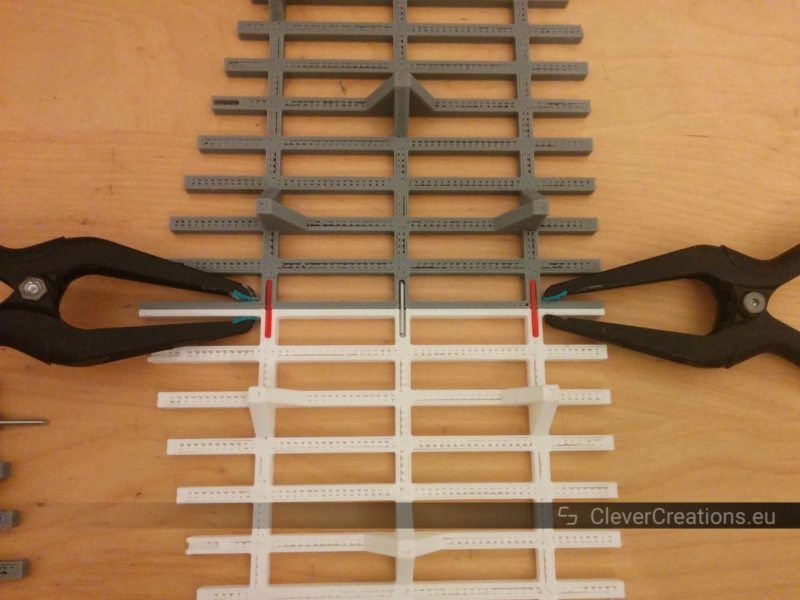 Two small clamps holding together two 3D printed grid elements.