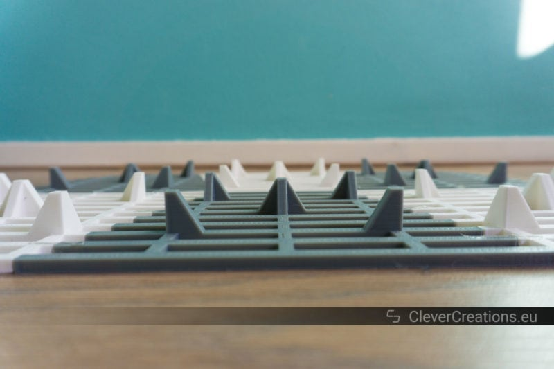 Side view of a custom 3D printed grey and white cat litter mat that has been placed upside down on a wooden floor.