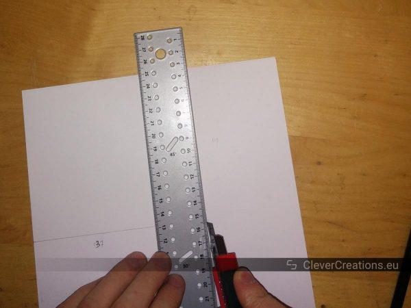 A hand holding a box cutter cutting a piece of A4 paper along a ruler.