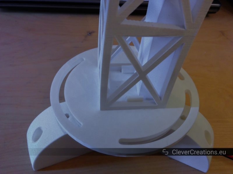 An assembly of white 3D printed parts that makes up the base of a rotating desk lamp.