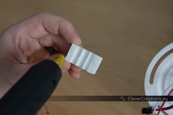 A hand holding a white plastic component while a hot glue gun squirts hot glue on the component.
