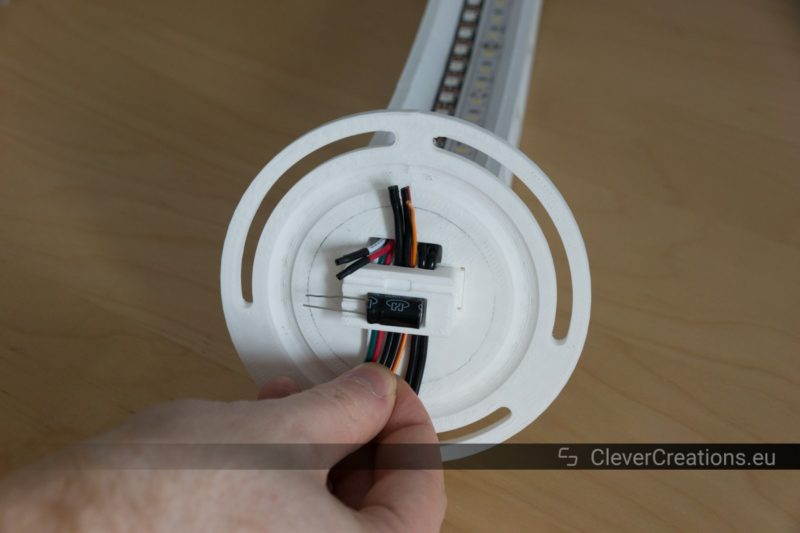A hand inserting wires through an empty channel in an assembly of parts from a custom 3D printed desk lamp.
