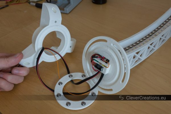 A hand holding a white component up so that the path that wires take through a 3D printed thrust bearing is clearly visible.