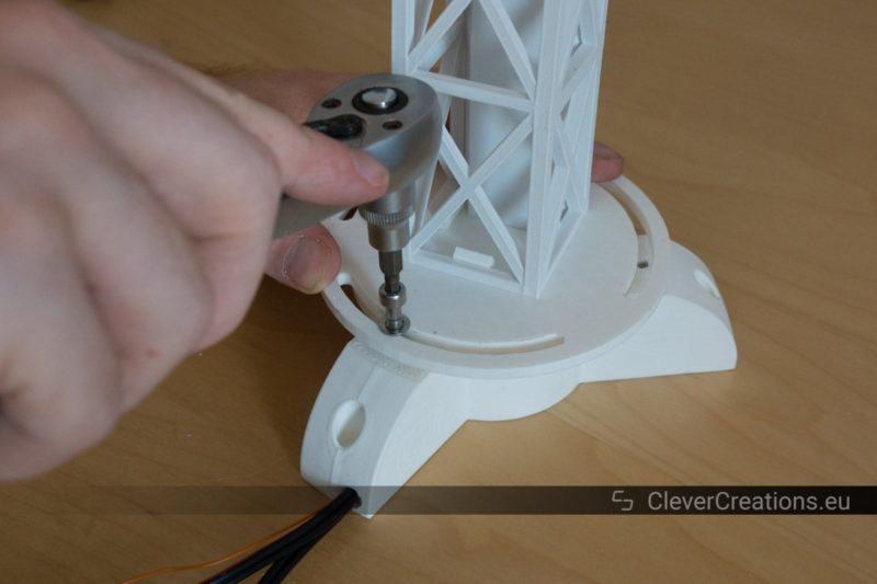 A hand holding a socket wrench that is being used to tighten a stainless steel M5 bolt on a white desk lamp assembly.