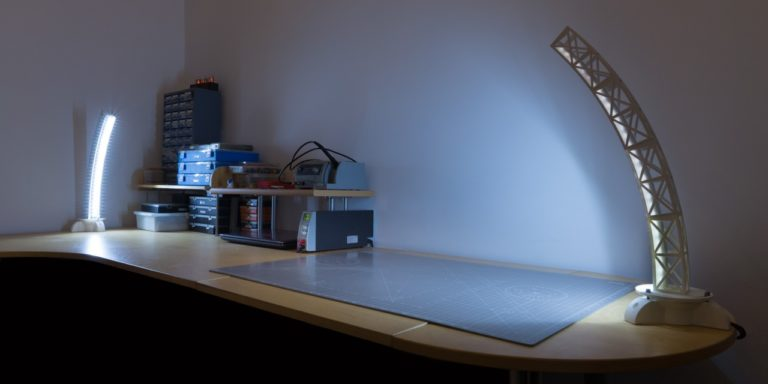 Two custom 3D printed rotating desk lamps on top of a desk with tools and containers.
