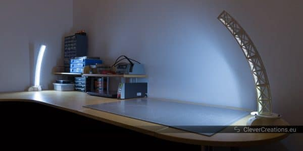 A workbench with two 3D printed rotatable desk lamps.