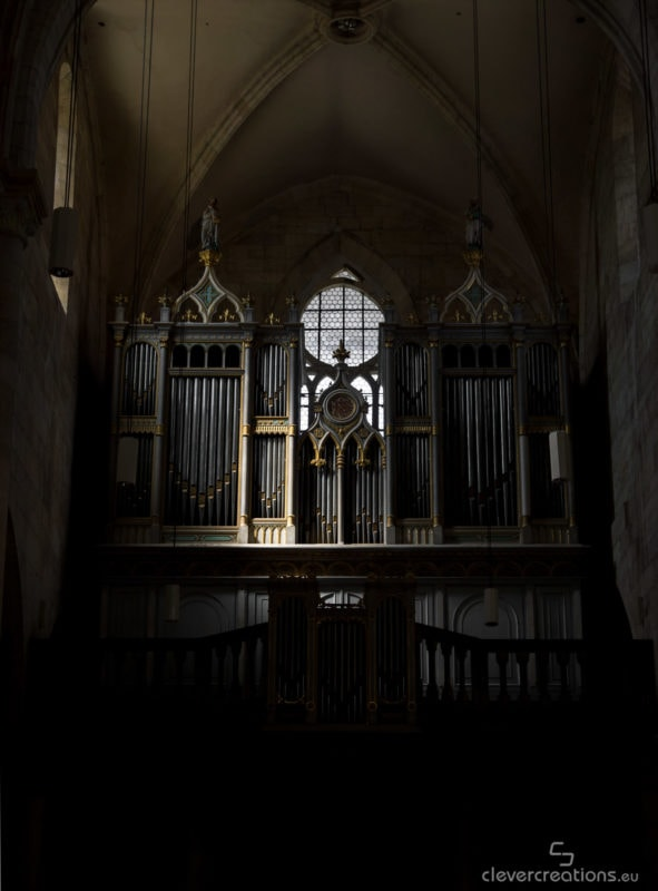 An organ lit by a ray of light in a darkened church.