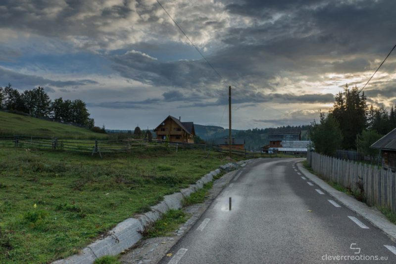 A house at the end of a wet road with a rising sun.