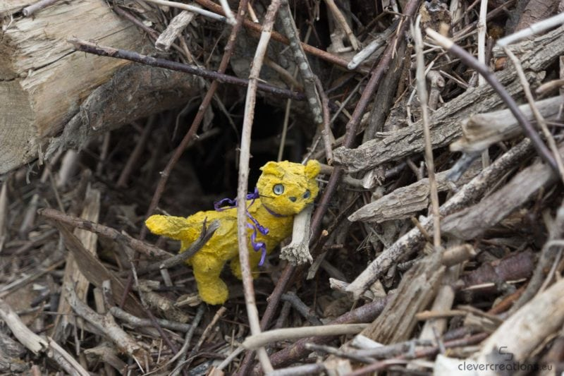 A toy cat stuck in driftwood.