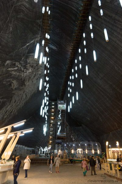 The interior of a salt mine with lights hanging from the ceiling and people walking on the ground.