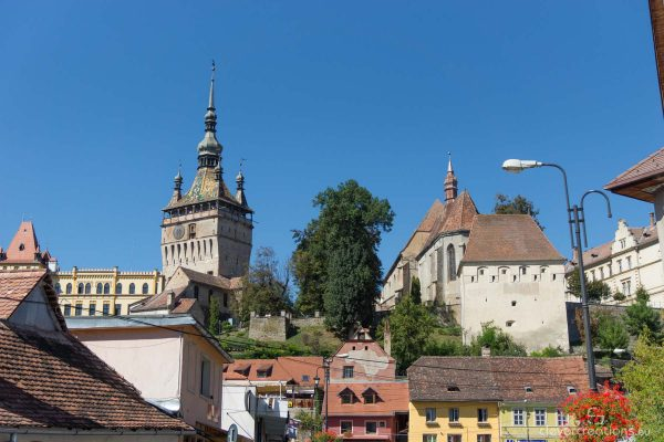 A city with an old clock tower and other buildings.