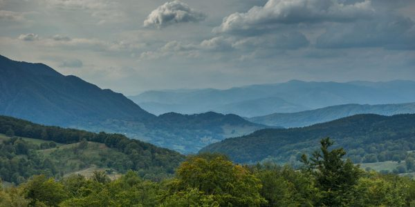 A beautiful landscape containing Romanian mountains, clouds and trees.