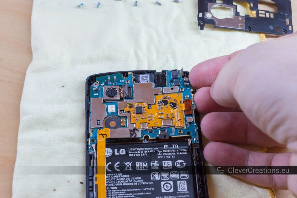 A hand carefully lifting the motherboard out of a LG Nexus 5 phone.