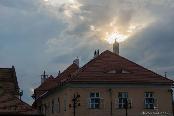 A rooftop of a house with the 'eyes of Sibiu', with a sun in the background.