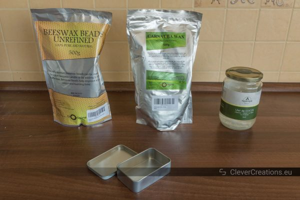 A bag of beeswax, a bag of carnauba wax, a jar of coconut oil and a storage tin on a counter top