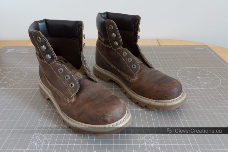 A pair of old scuffed leather boots without shoe laces.
