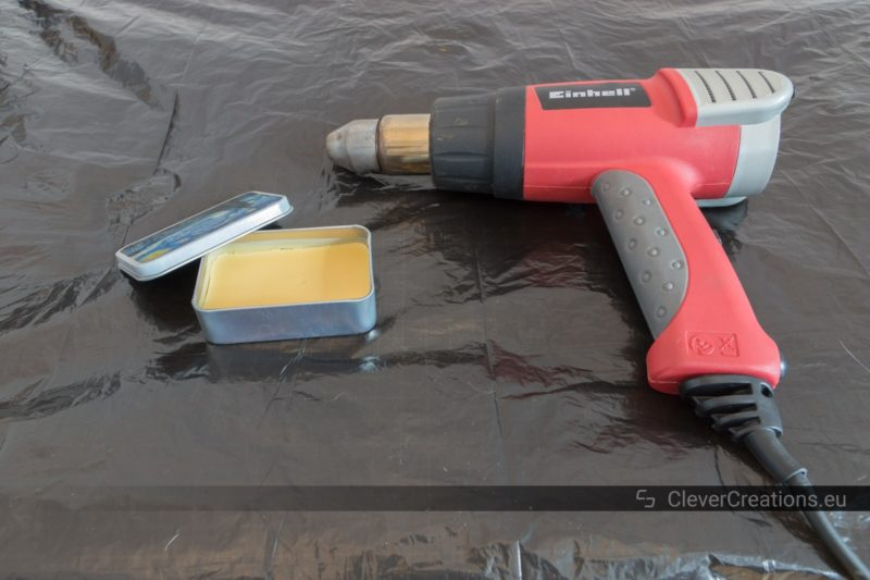 A tin container with shoe care wax and a hot air gun on top of a surface covered with a garbage bag.