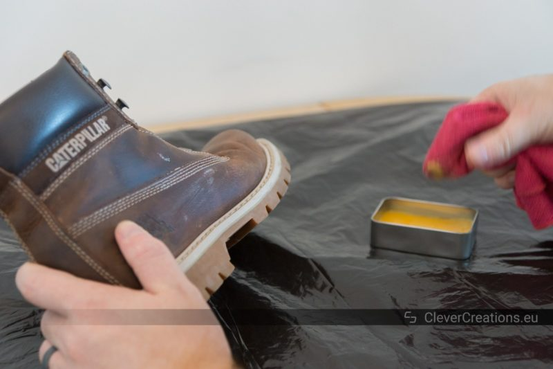 A hand holding a red microfiber cloth that is being dipped in liquid shoe care wax with a scuffed discolored leather shoe being held by another hand.