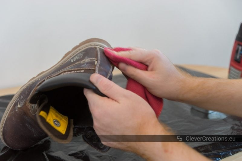 A microfiber cloth with rubbing shoe care wax being rubbed on a scuffed discolored leather boot.