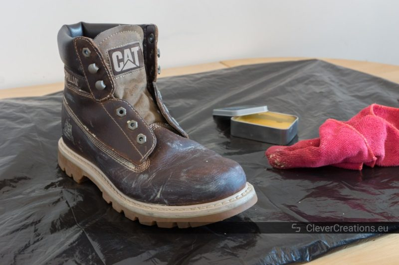 A leather boot covered in shoe care wax with in the background a microfiber cloth and a tin container with shoe care wax.