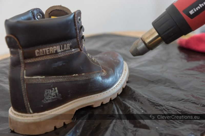 A hot air gun blowing hot air on a leather boot. Shoe care wax is melting on the leather boot.