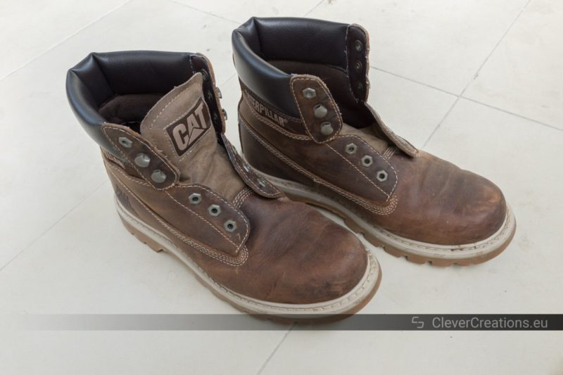 A pair of scuffed up and discolored leather boots.