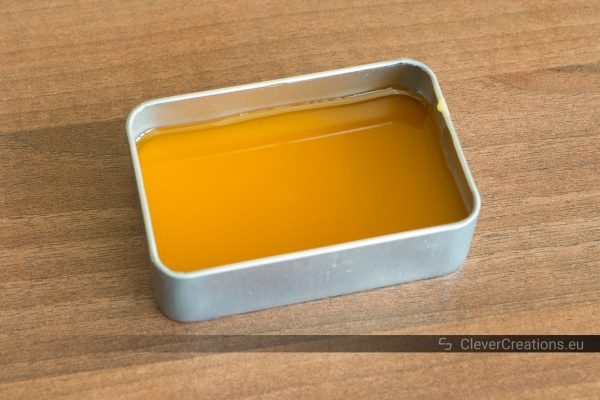 Liquid shoe wax in a tin storage container without lid that is placed on a wooden surface.