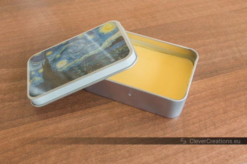 Solidified wax for shoes in a tin storage container with a lid positioned hanging over the edge.