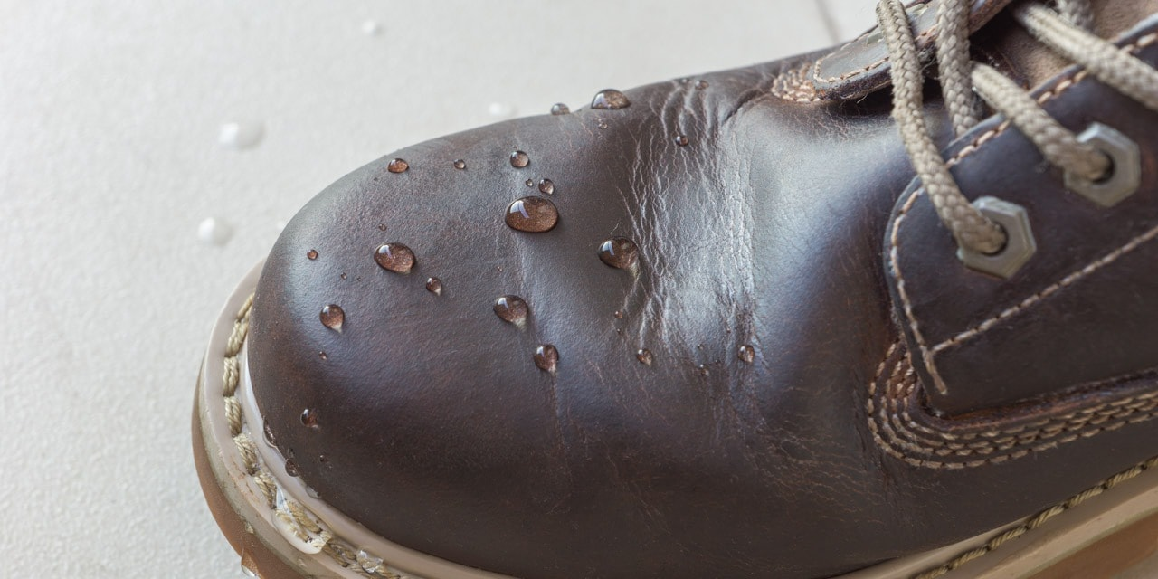 A close-up of water droplets on top of a waterproofed leather shoe.