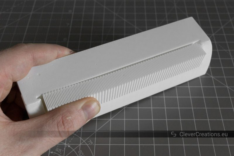 A hand removing support material from a white 3D printed handle.