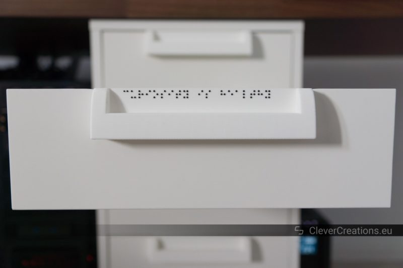 Front view of an extended drawer on a white IKEA ALEX drawer unit, with a 3D printed handle and white label with braille text.