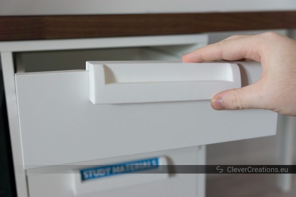 A hand placing a white 3D printed handle on the extended drawer of an IKEA ALEX unit.