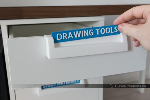 "A hand inserting a label with the text ""Drawing Tools"" in a 3D printed handle on an IKEA ALEX drawer."